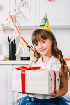 Portret van een glimlachend meisje die witte verpakte giftdoos houden die met rood lint op haar verjaardag wordt gebonden