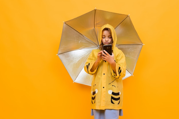 Portret van een glimlachend meisje in een mooie gele raincoatabij die een zilveren paraplu en met een telefoon in haar handen op een gele muur houdt