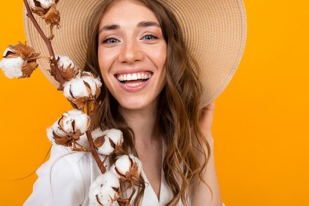 Portret van een glimlachend meisje met een zomerhoed met een twijg van katoen over geel