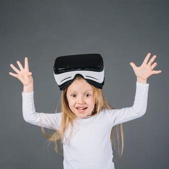 Portret van een glimlachend meisje met virtuele werkelijkheidsglazen op haar hoofd dreigend gebrul