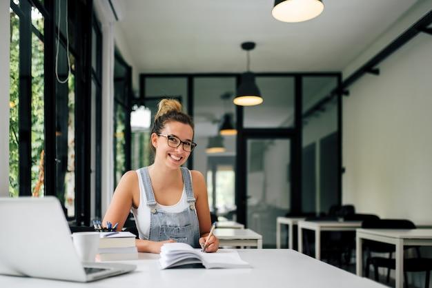 Portret van een glimlachend millenial meisje dat in moderne studeerkamer bestudeert.