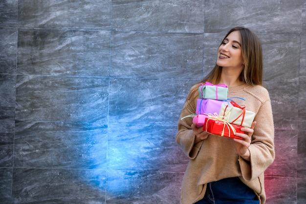 Portret van een glimlachend mooi meisje dat een stapel geschenkdozen vasthoudt over een grijze achtergrond