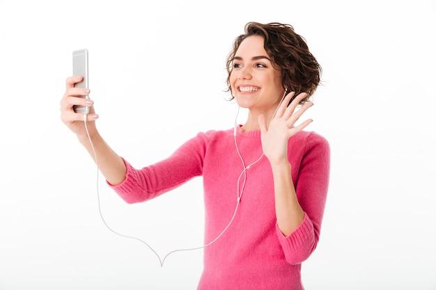 Portret van een glimlachend mooi meisje met oortelefoons