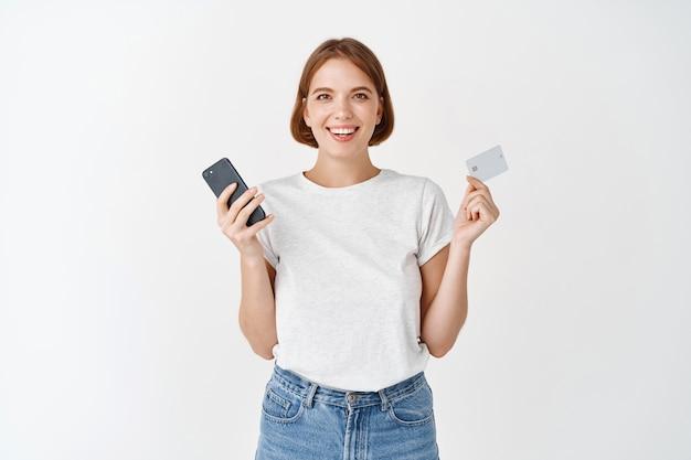Portret van een glimlachend natuurlijk meisje dat een mobiele telefoon en een plastic creditcard toont, online betaalt, tegen een witte muur staat