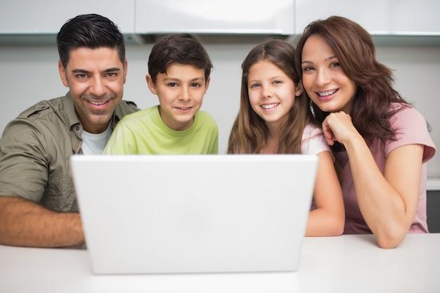 Portret van een glimlachend paar met jonge geitjes die laptop met behulp van