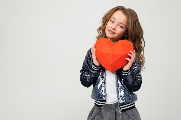 Portret van een glimlachend stijlvol kaukasisch meisje dat een rood document hart op een witte muur met lege ruimte houdt