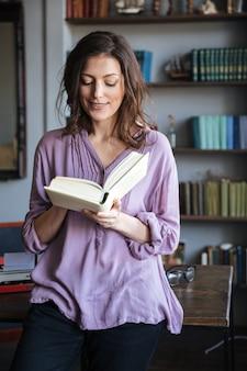 Portret van een glimlachend toevallig rijp boek van de vrouwenlezing