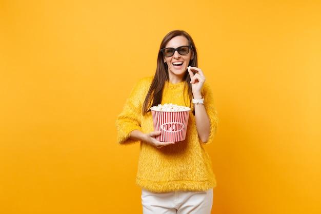 Portret van een glimlachend vogue-jong meisje in een 3d imax-bril die filmfilm kijkt en een emmer popcorn vasthoudt die op een felgele achtergrond wordt geïsoleerd. mensen oprechte emoties in de bioscoop, lifestyle concept.