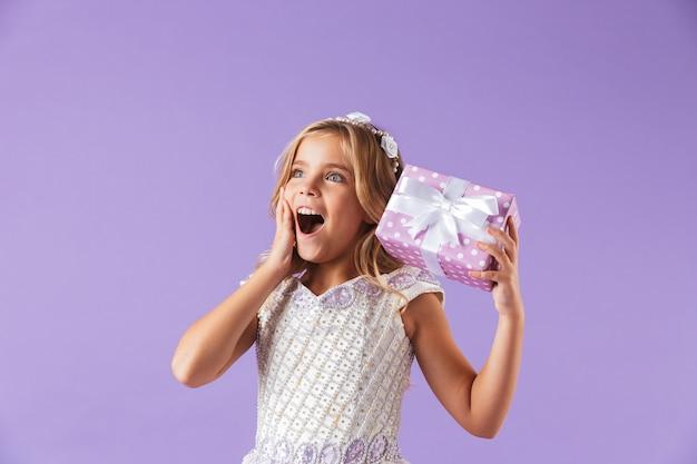 Portret van een glimlachend vrolijk mooi meisje gekleed in een prinsessenjurk die over violette muur wordt geïsoleerd, die huidige doos houdt