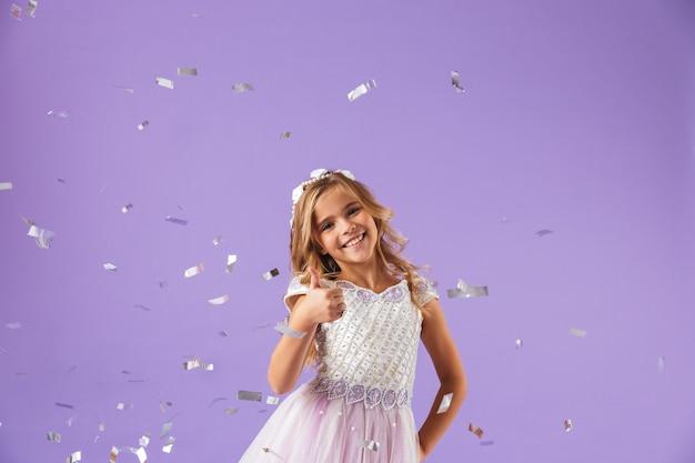 Portret van een glimlachend vrolijk mooi meisje gekleed in een prinsessenjurk geïsoleerd over violette muur, duimen opdagen