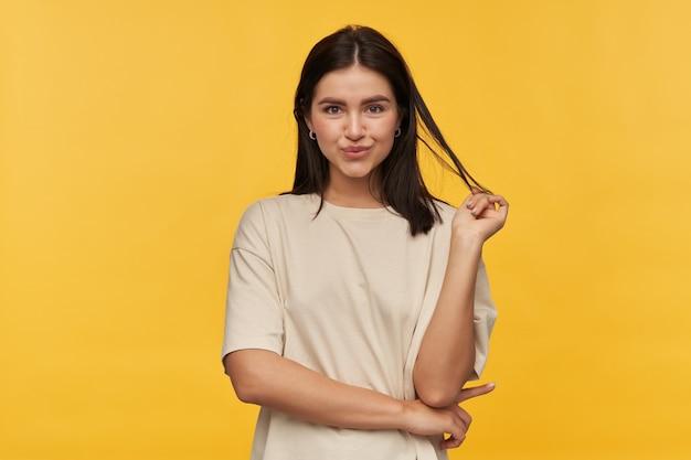 Portret van een glimlachende aantrekkelijke jonge vrouw in een wit t-shirt die staat en haar donkere haar aanraakt over een gele muur