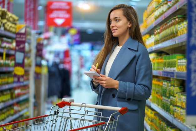 Portret van een glimlachende aantrekkelijke jonge vrouwenkoper met kar in de supermarktdoorgang met kruidenierswinkellijst tijdens het winkelen voedsel