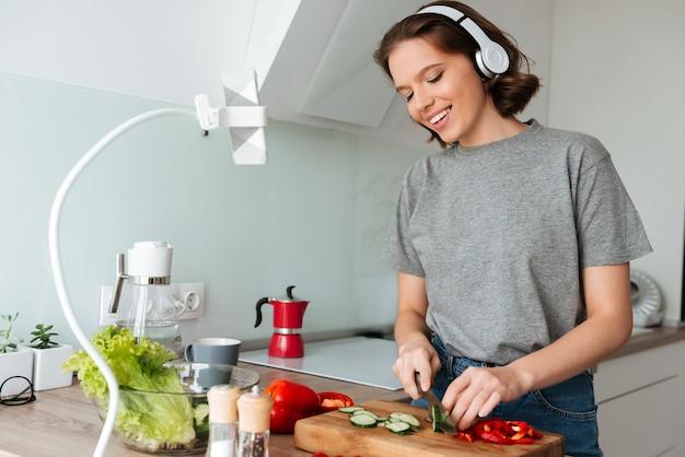 Portret van een glimlachende aantrekkelijke vrouw die aan muziek luistert