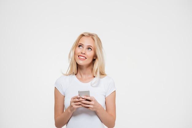 Portret van een glimlachende aantrekkelijke vrouw die mobiele telefoon houdt