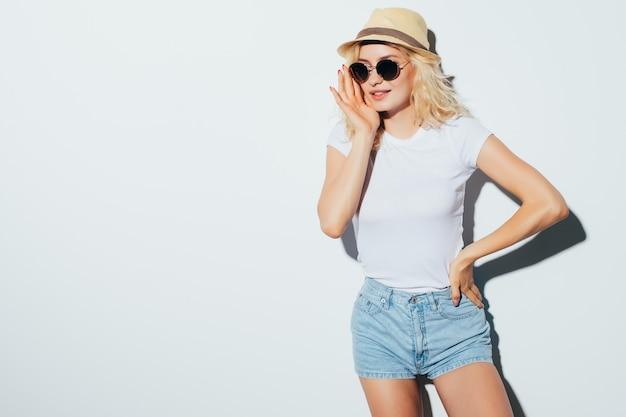 Portret van een glimlachende aantrekkelijke vrouw in zonnebril, zomerkleding en hoed die terwijl status geïsoleerd over witte muur stelt