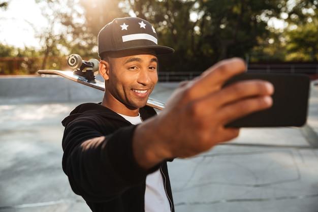 Portret van een glimlachende afrikaanse mannelijke tiener die een selfie neemt