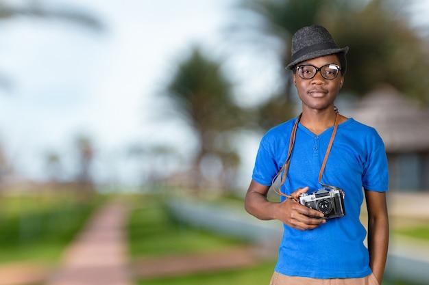 Portret van een glimlachende afro amerikaanse mens die foto op retro camera maakt