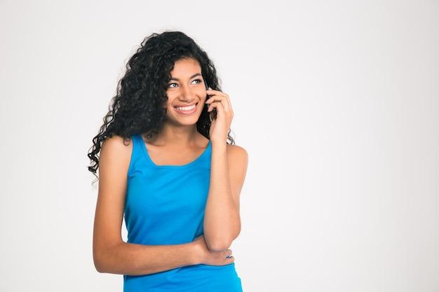 Portret van een glimlachende afro-amerikaanse vrouw die aan de telefoon spreekt en weg kijkt die op een witte muur wordt geïsoleerd