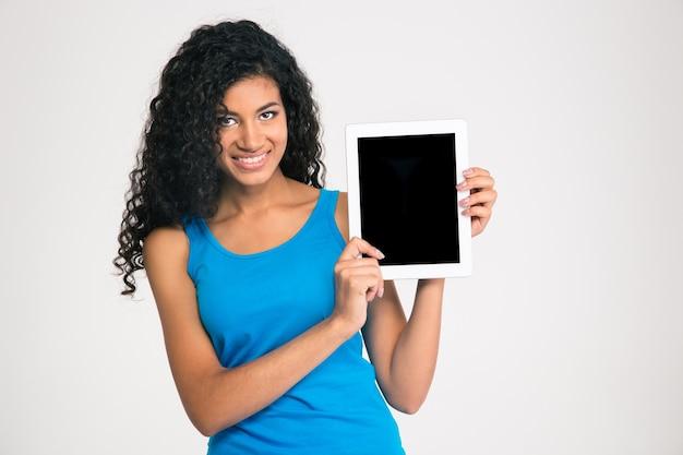 Portret van een glimlachende afro-amerikaanse vrouw die het lege scherm van de tabletcomputer toont dat op een witte muur wordt geïsoleerd