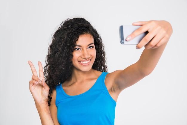 Portret van een glimlachende afro-amerikaanse vrouw die selfiefoto maakt terwijl twee vingers wordt getoond teken dat op een witte muur wordt geïsoleerd