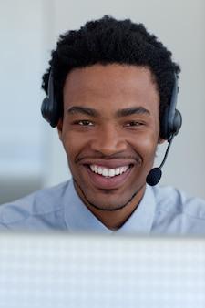 Portret van een glimlachende afro-amerikaanse zakenman in een call centre
