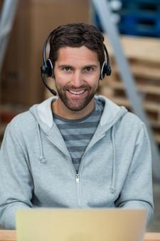 Portret van een glimlachende arbeider die een hoofdtelefoon draagt
