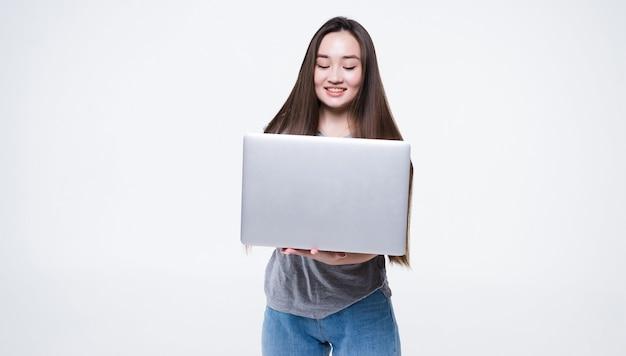 Portret van een glimlachende aziatische laptop van de vrouwenholding die op grijze muur wordt geïsoleerd