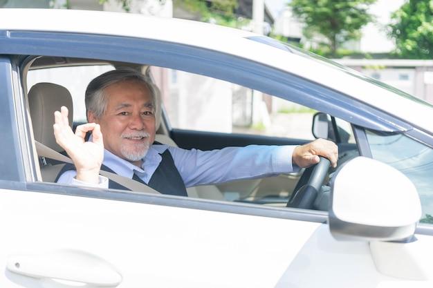 Portret van een glimlachende aziatische senior man, oude man, oudere man die een auto bestuurt
