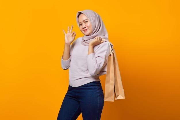 Portret van een glimlachende aziatische vrouw die boodschappentassen vasthoudt en een goed teken maakt met vingers over gele achtergrond