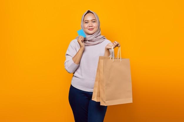Portret van een glimlachende aziatische vrouw die een boodschappentas vasthoudt en een creditcard toont over een gele achtergrond