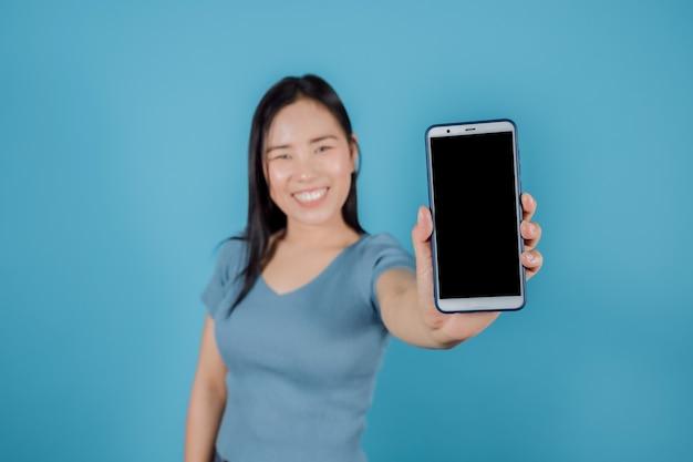 Portret van een glimlachende aziatische vrouw die een mobiele telefoon met een leeg scherm toont terwijl ze op een blauwe achtergrond staat. selectieve focus