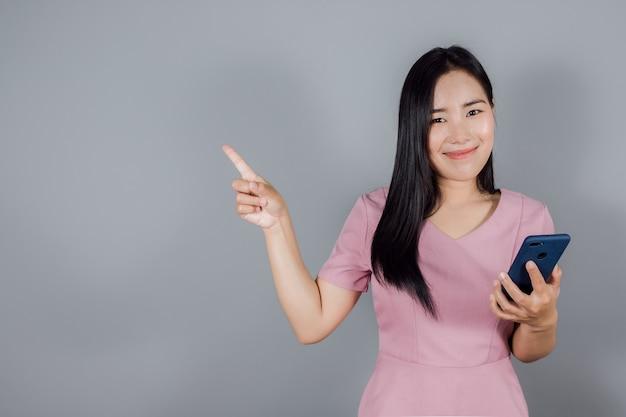 Portret van een glimlachende aziatische zakenvrouw die een smartphone vasthoudt en met de vinger naar de zijkant wijst op een grijze achtergrond met kopieerruimte