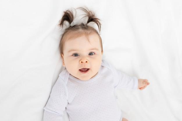 Portret van een glimlachende baby op het bed thuis, het concept van een gelukkige liefdevolle familie en kinderen