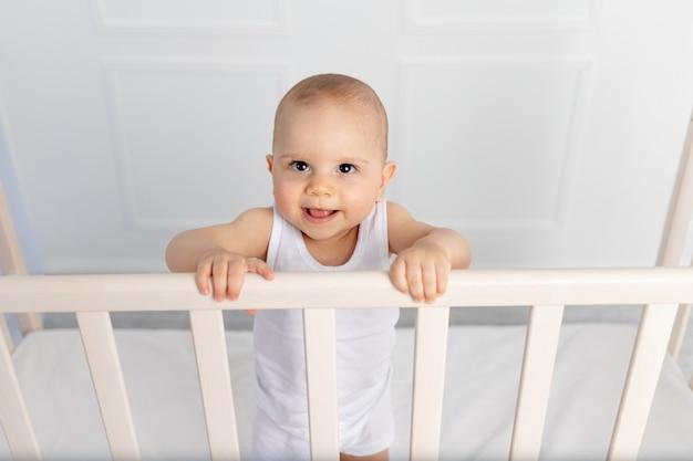 Portret van een glimlachende babyjongen 8 maanden oud die zich in een wieg in een kinderkamer in witte kleren en l, ochtendbaby, babyproductenconcept bevinden