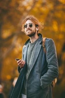 Portret van een glimlachende bebaarde man in oortelefoons