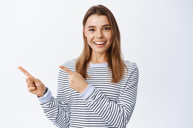 Portret van een glimlachende blanke vrouw met blond haar, met een goede dealaanbieding, met de vingers naar links wijzend naar de logobanner en naar de voorkant kijkend, richting of weg wijzend, witte muur