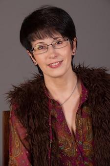Portret van een glimlachende blanke vrouw van middelbare leeftijd tegen grijze muur.