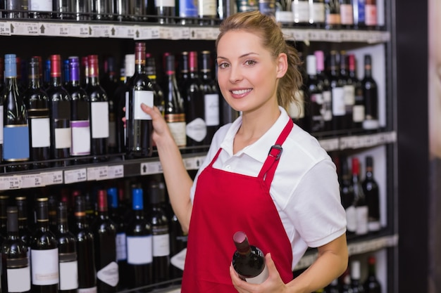 Portret van een glimlachende blonde arbeider die een wijnfles neemt