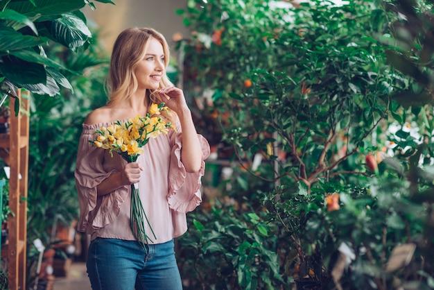 Portret van een glimlachende blonde jonge vrouw die gele bloem houdt weg kijkend