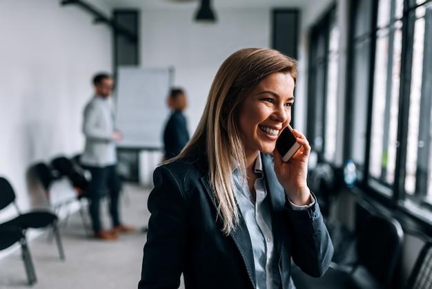 Portret van een glimlachende blonde onderneemster die op een telefoon tijdens de onderbreking van een vergadering spreekt.