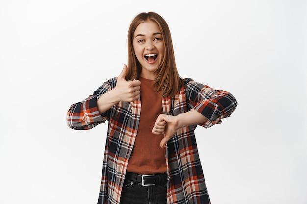 Portret van een glimlachende blonde vrouw die duimen op en neer laat zien, een hekel aan gebaar heeft, iets beoordeelt, goedkeurt of afkeurt, staande tegen een witte muur