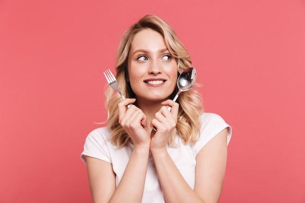 Portret van een glimlachende blonde vrouw met een casual t-shirt met lepel en vork geïsoleerd over roze muur