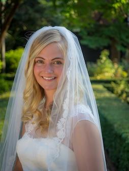 Portret van een glimlachende bruid in een tuin omgeven door groen onder het zonlicht