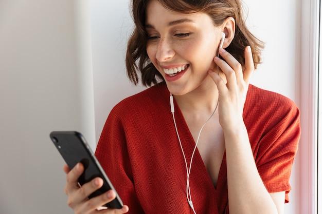 Portret van een glimlachende brunette vrouw gekleed in vrijetijdskleding die naar muziek luistert met smartphone en oortelefoons terwijl ze thuis boven het raam zit
