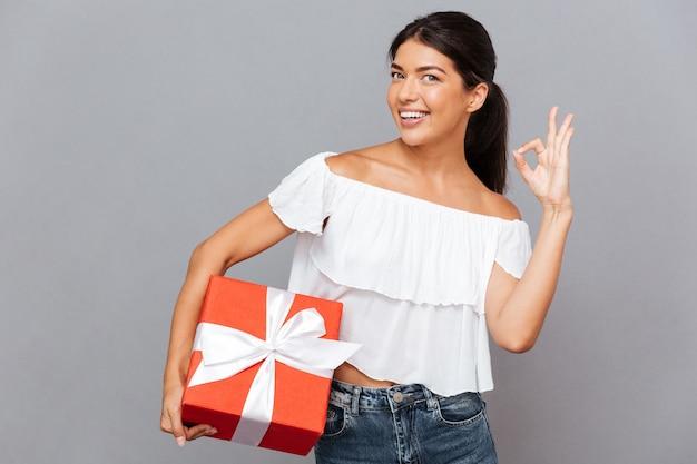 Portret van een glimlachende casual vrouw die een geschenkdoos vasthoudt en een goed teken toont dat op een grijze muur is geïsoleerd