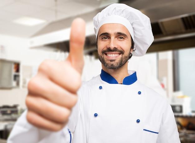 Portret van een glimlachende chef-kok die duimen opgeeft