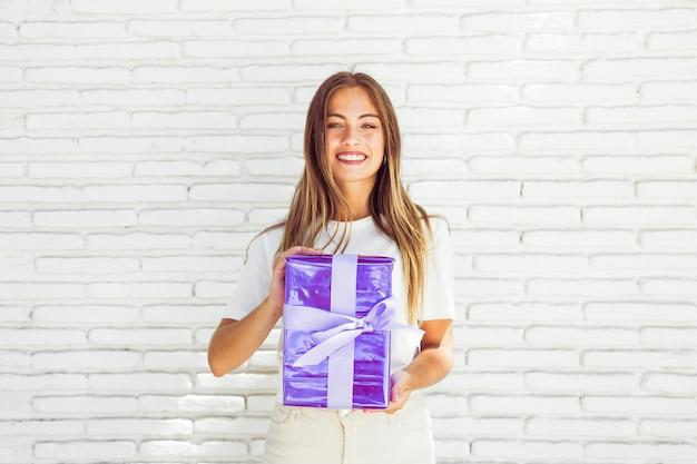 Portret van een glimlachende de giftdoos van de vrouwenholding voor bakstenen muur