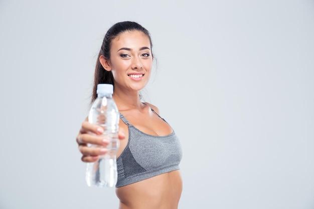 Portret van een glimlachende de holdingsfles van de geschiktheidsvrouw met water dat op een witte muur wordt geïsoleerd