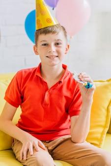 Portret van een glimlachende de partijhoorn van de jongensholding