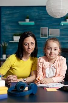 Portret van een glimlachende familie die in de camera kijkt terwijl ze aan het bureau zit
